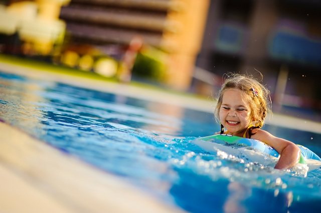 A Girl Swimming in Outdoor Pool